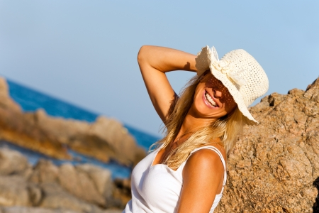 Close up portrait of Young woman smiling under straw hat on beach  photo