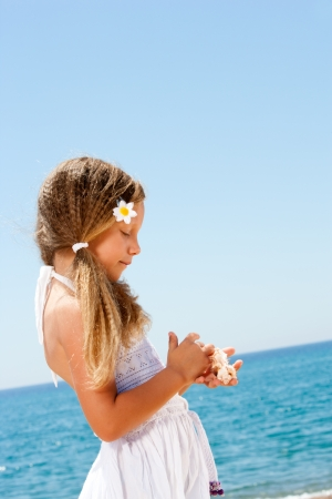 Cute girl in white dress holding shells on sunny beach  photo
