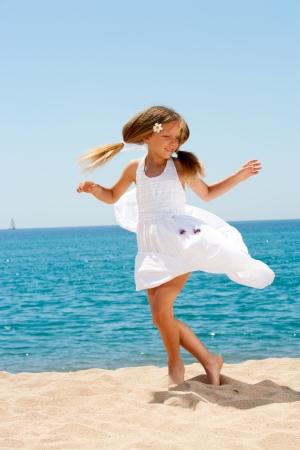 little girl dancing: Cute girl in white dress dancing  on sunny beach