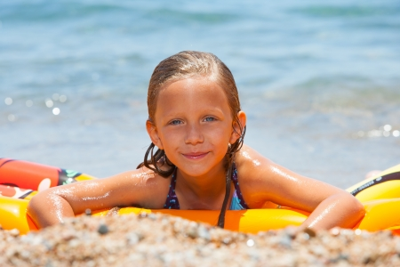 beach mat: Cute girl having fun on air mattress on beach