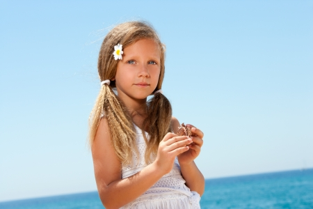 Portrait of sweet girl in white dress holding a shell  photo