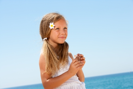 Close up portrait of smiling girl in white dress at seaside  photo
