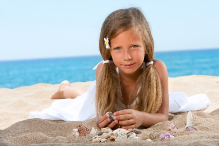 Close up portrait of Sweet girl playing with shells on beach