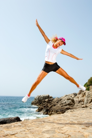 sportsmanship: Attractive energetic woman in sportswear jumping at seaside  Stock Photo