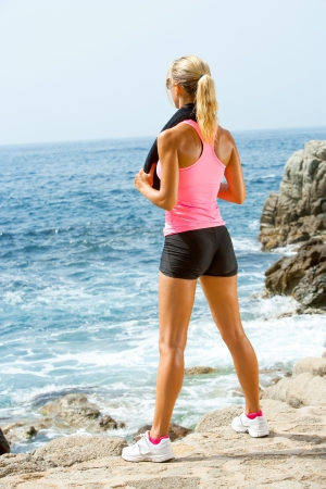 seasides: Young attractive woman looking at sea after fitness workout.