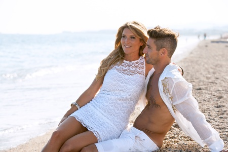 blonde couple: Close up portrait of Attractive couple in white sitting on pebble beach