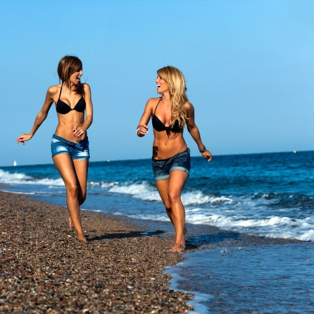 Attractive two young girl friends running along seside