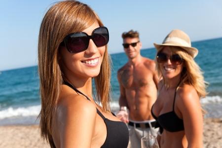 homem: Feche acima do retrato da menina atrativa com os amigos na praia