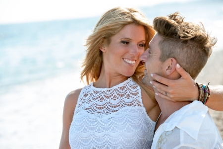 Close up portrait of romantic couple in white on beach  Stock Photo - 15388571