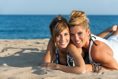 femal: Close up portrait of two attractive femal friends on beach