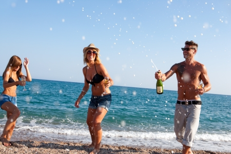 boys party: Group of friends dancing under champagne bubbles on beach