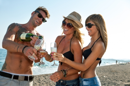 beach wear: Group of handsome young friends having champagne on beach