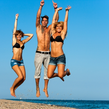 Energetic group of young friends jumping on beach  photo