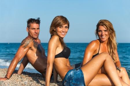 tattooed: Group portrait of three attractive friends sitting on beach  Stock Photo