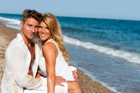 Portrait of handsome couple in white sitting on beach  photo
