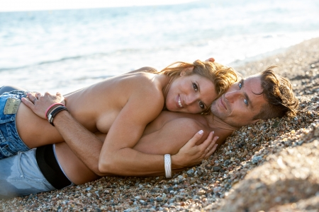 intymno: Przystojny romantyczny para obejmując na kamienistej plaży