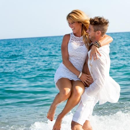 parejas enamoradas: Feliz pareja vestida de blanco jugando en las olas Foto de archivo