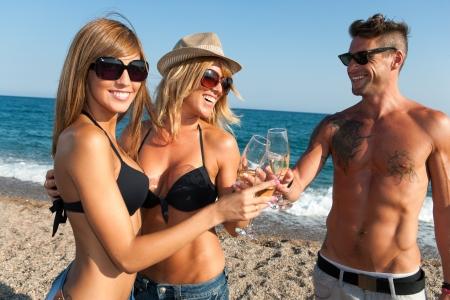 brindis champan: Feliz grupo de j�venes amigos haciendo un brindis con champ�n en la playa Foto de archivo