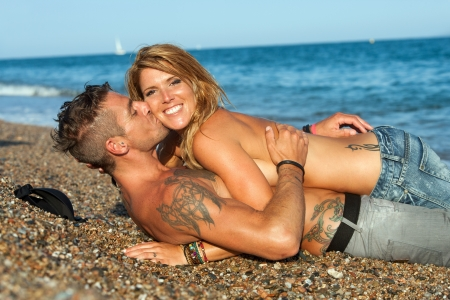 tatouage sexy: Young attractive couple sexy embrassant sur la plage de galets