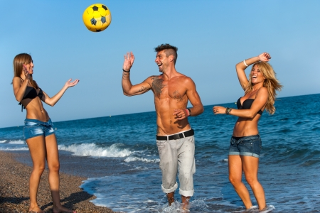 Three handsome friends playing with inflatable ball on beach