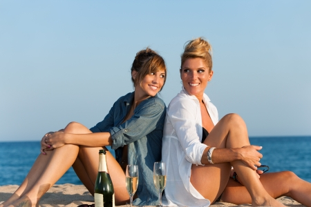 Portrait of two attractive girls sitting back to back on beach  photo