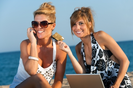 Two attractive girlfriends shopping on line with credit card at beach  photo