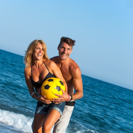 casualness: Portrait of young couple having fun with ball on beach