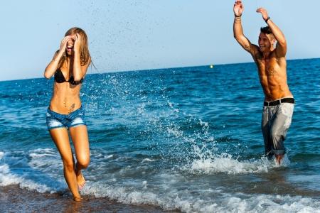 soleil rigolo: Jeune couple ayant une grande �claboussures d'eau de temps � bord de la mer