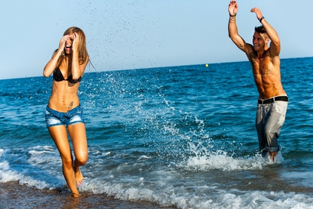 having fun: Young couple having great time splashing water at seashore  Stock Photo