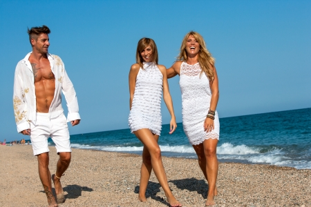 casualness: Group of young friends dressed in white wandering along sunny beach