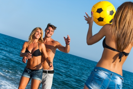 beach volleyball: Young group of friends having fun with ball game on beach  Stock Photo