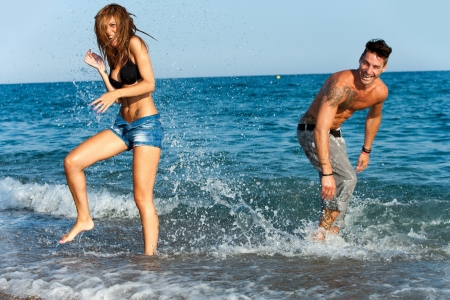 Attractive young couple having fun splashing water on beach  photo
