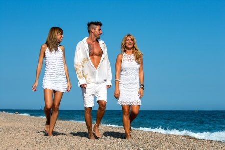 casualness: Young group of friends dressed in white wandering along sunny beach