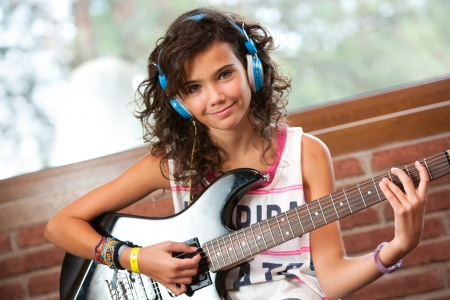 Portrait of cute teenager girl at guitar practice at home. photo