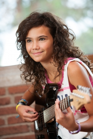 Close up portrait of cute girl playing guitar indoors  photo