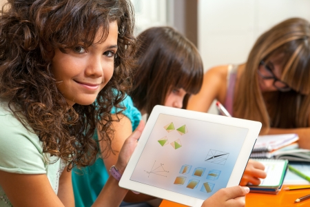 digital school: Close up portrait of cute young student holding tablet with homework
