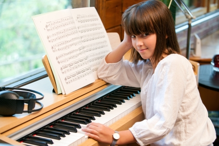Close up portrait of little girl sitting at piano. photo
