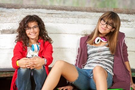 girl headphones: Close up portrait of two cute teenage girlfriends sitting outdoors