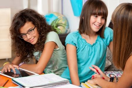 adolescentes estudiando: Tres estudiantes adolescentes que discuten su tarea en el escritorio. Foto de archivo