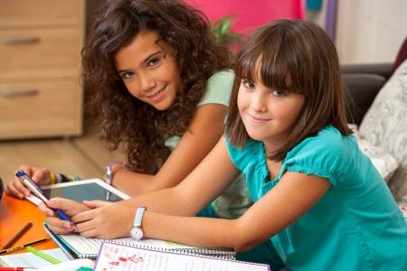 niños estudiando: Dos adolescentes haciendo homewotk en casa.