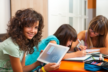 Young teenage girl with classmates showing homework on digital tablet. photo