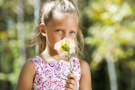 contentedness: Close up portrait of blue eyed girl hiding behind flower oudoors.