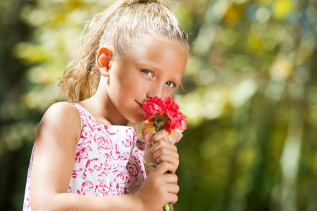 contentedness: Close up portrait of blue eyed girl smelling flower outdoors.