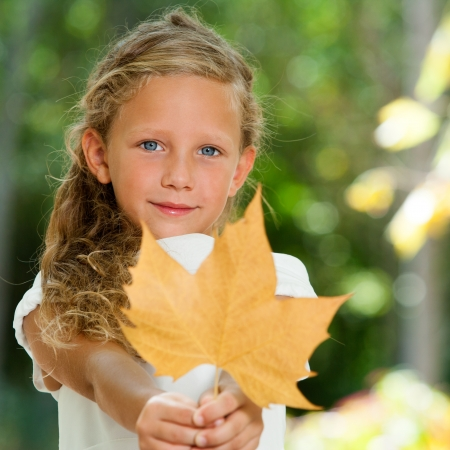 Close up portrait of blue eyed girl holding dry leaf in garden. photo