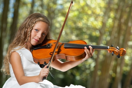 Close up portrait of young cute violinist playing in the woods. photo