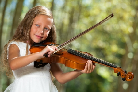 Close up portrait of cute girl in white playing violin outdoors. photo