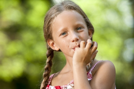 Portrait of cute girl licking off chocolate fingers outdoors.