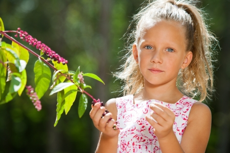 contentedness: Close up portrait of cute girl outdoors picking wild berries.