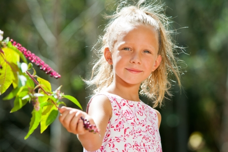 contentedness: Close up portrait of cute girl picking wild berries in forest. Stock Photo