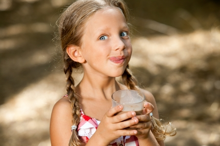 one child: Close up portrait of expressive girl drinking chocolate milkshake.